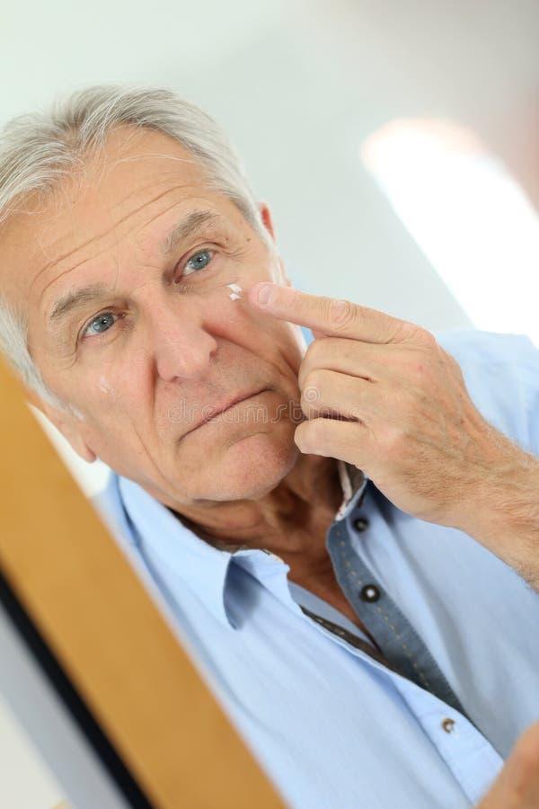 Porträt des älteren Mannes Antialterncreme auftragend stockbild