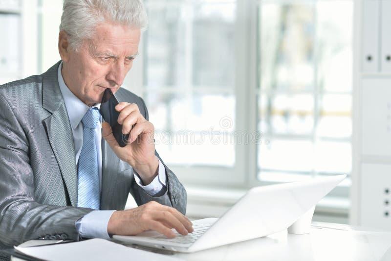 Porträt des älteren Mannes, der Laptop im Büro verwendet stockbild