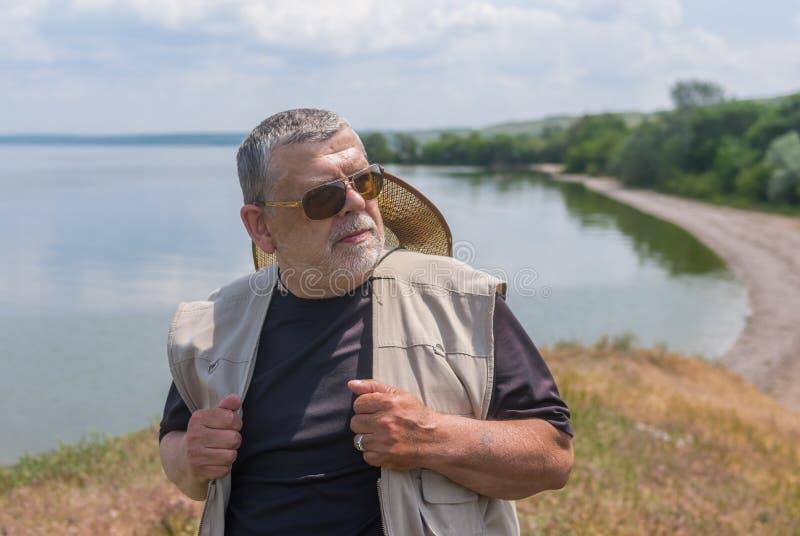 Porträt des älteren Mannes dunkle Sonnenbrille und den Strohhut tragend, die auf Dnipro-Flussufer an der Sommersaison steht lizenzfreie stockbilder