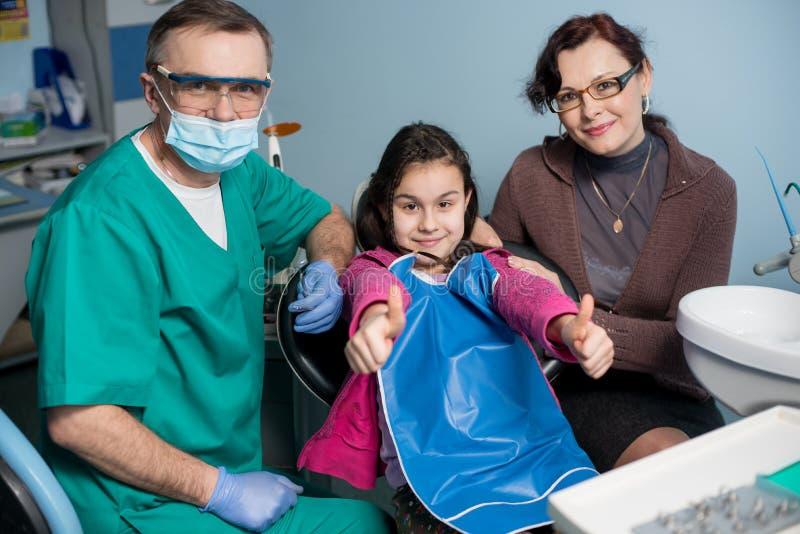 Porträt des älteren pädiatrischen Zahnarztes und des Mädchens mit ihrer Mutter auf dem ersten zahnmedizinischen Besuch im zahnmed lizenzfreies stockfoto