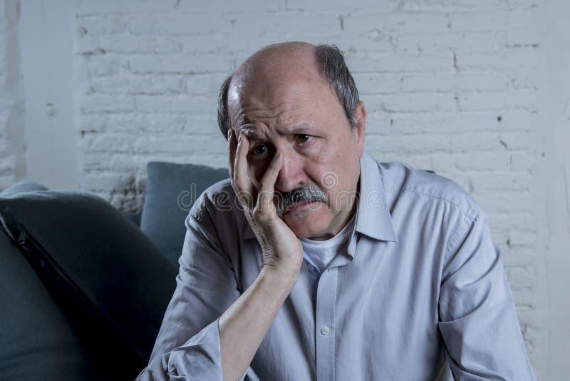 Porträt des älteren reifen alten Mannes auf seinen zu Hause allein traurigen und besorgten leidenden Schmerz des Gefühls der Couc stockbild