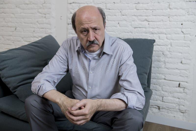 Porträt des älteren reifen alten Mannes auf seinen zu Hause allein traurigen und besorgten leidenden Schmerz des Gefühls der Couc stockbilder