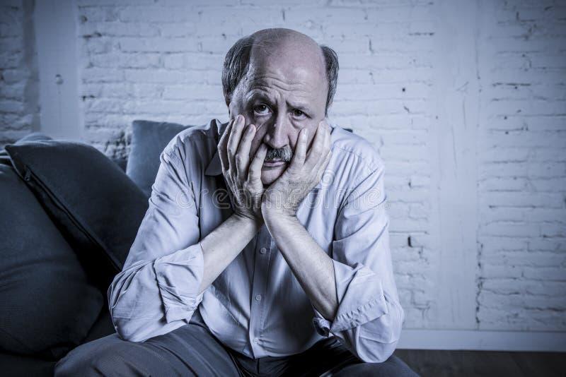 Porträt des älteren reifen alten Mannes auf seiner zu Hause Couch 60s allein lizenzfreies stockbild