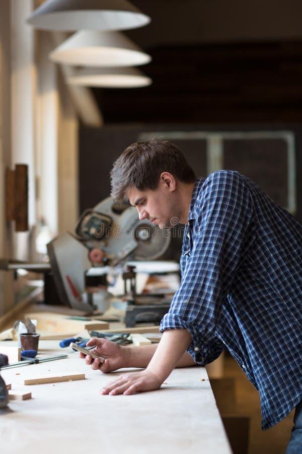 Porträt des älteren Tischlers arbeitend an seiner Werkstatt während Aufenthalt lizenzfreies stockbild