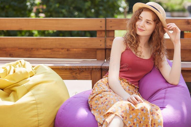 Porträt des Überraschens der jungen Frau mit nachdenklichem Gesichtsausdruck, tragendem Hut, T-Shirt und Rock, beiseite lächelnd  lizenzfreie stockfotos