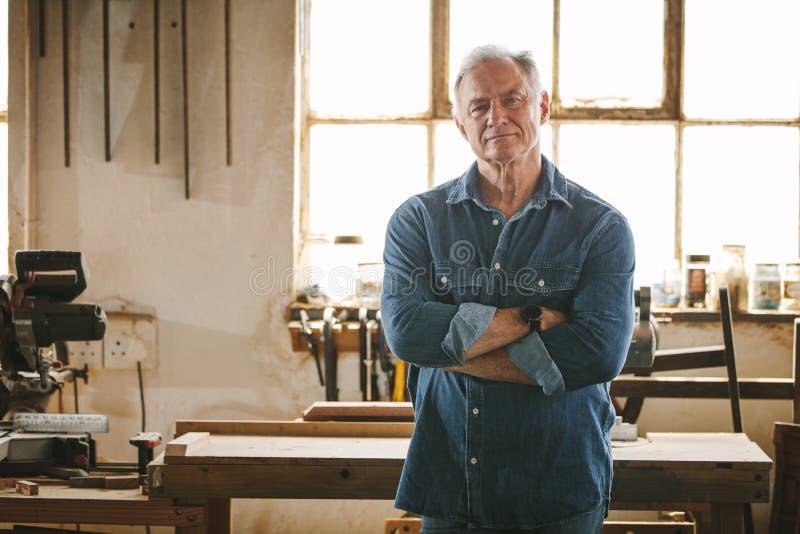 Porträt des überzeugten älteren männlichen Tischlers lizenzfreie stockbilder
