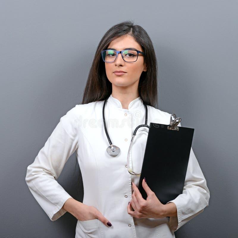 Porträt des überzeugten Arztfrauenholdingklemmbrettes gegen grauen Hintergrund stockbild