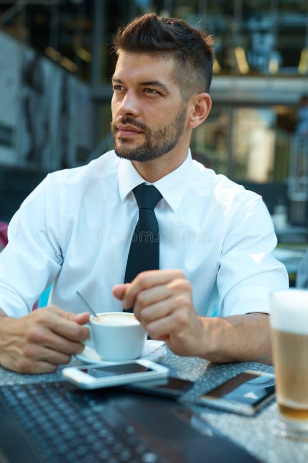 Porträt des überzeugten Geschäftsmannes draußen im Café lizenzfreie stockfotos