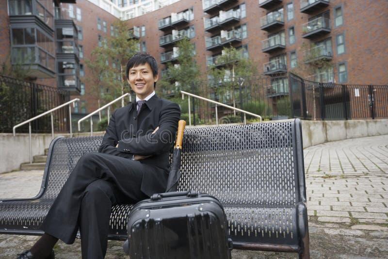 Porträt des überzeugten Geschäftsmannes mit dem Gepäck, das auf Bank gegen Gebäude sitzt stockfotos