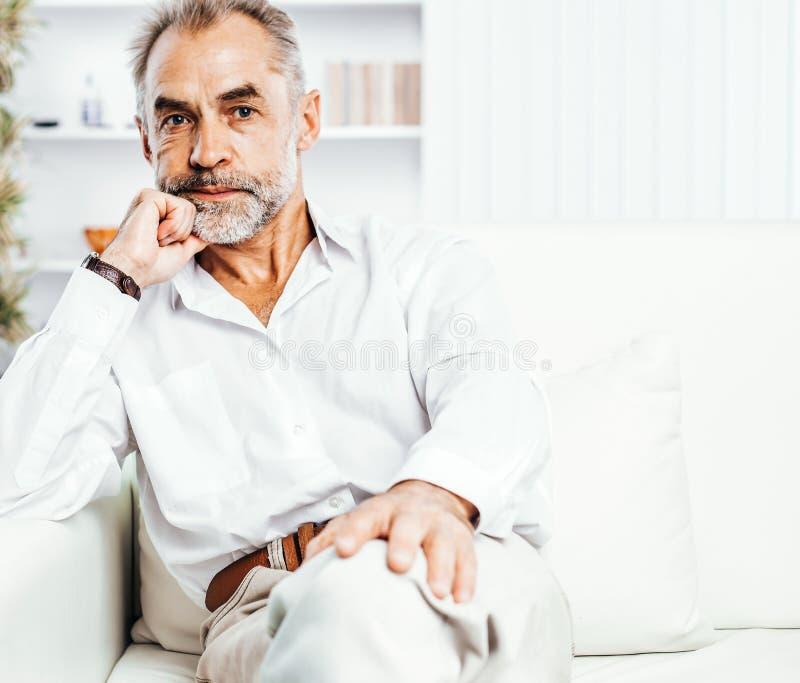 Porträt des überzeugten Geschäftsmannes weg sitzend auf Couch in hellem stockfotos