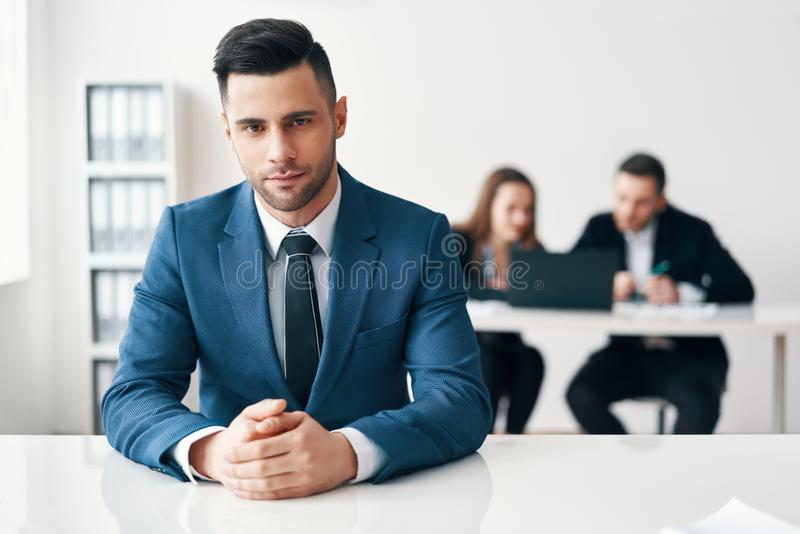 Porträt des überzeugten hübschen Geschäftsmannes, der im Büro mit seinem Geschäftsteam auf Hintergrund sitzt lizenzfreies stockfoto