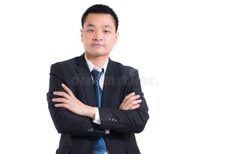 Porträt des überzeugten jungen asiatischen Geschäftsmannes, der mit den Armen gefaltet steht Geschäftsmannschwarz-Anzugsarme gekr stockfotos