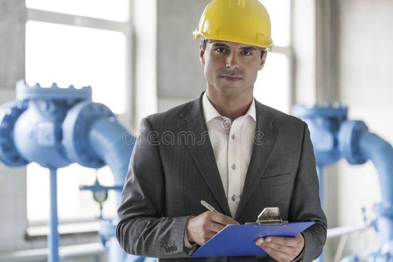 Porträt des überzeugten jungen männlichen Aufsichtskraftschreibens auf Klemmbrett in der Industrie lizenzfreie stockfotos