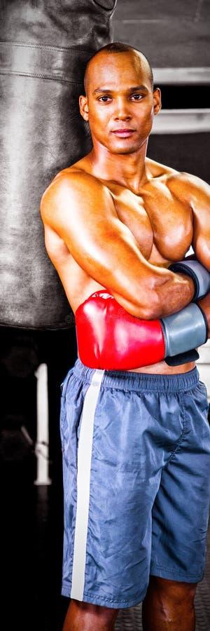 Porträt des überzeugten männlichen Boxers, der mit den Armen steht, kreuzte durch Sandsack lizenzfreie stockfotos