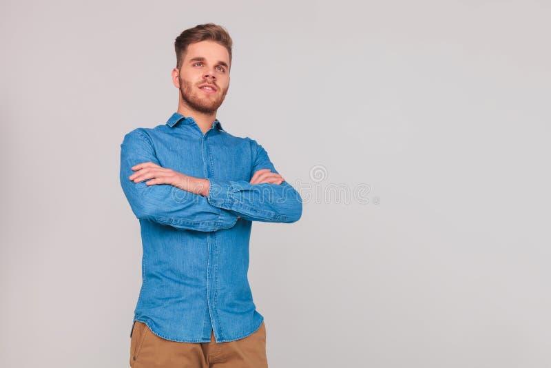 Porträt des überzeugten zufälligen Mannes, der oben zur Seite schaut stockfotografie