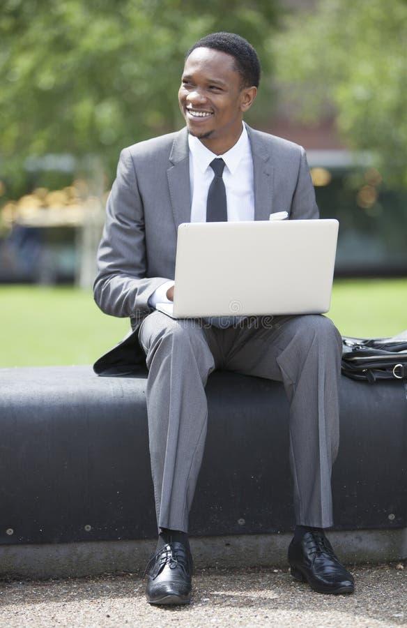 Porträt des Afroamerikaner-Geschäftsmannes draußen arbeitend an einem Laptop stockfotografie