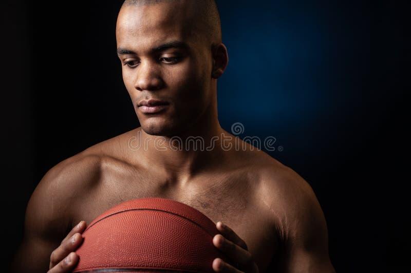 Porträt des afroen-amerikanisch männlichen Basketball-Spielers mit einem Ball stockfotos