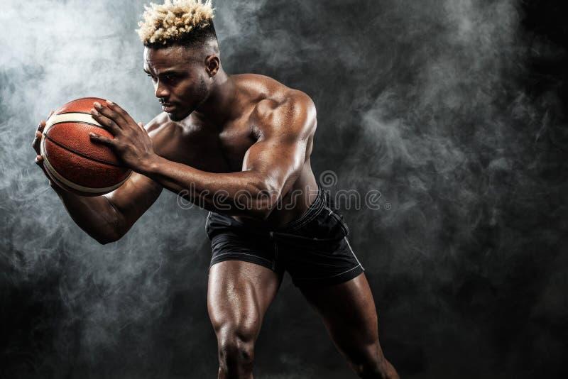 Porträt des afroen-amerikanisch Sportlers, Basketball-Spieler mit einem Ball über schwarzem Hintergrund Geeigneter junger Mann in stockfotos
