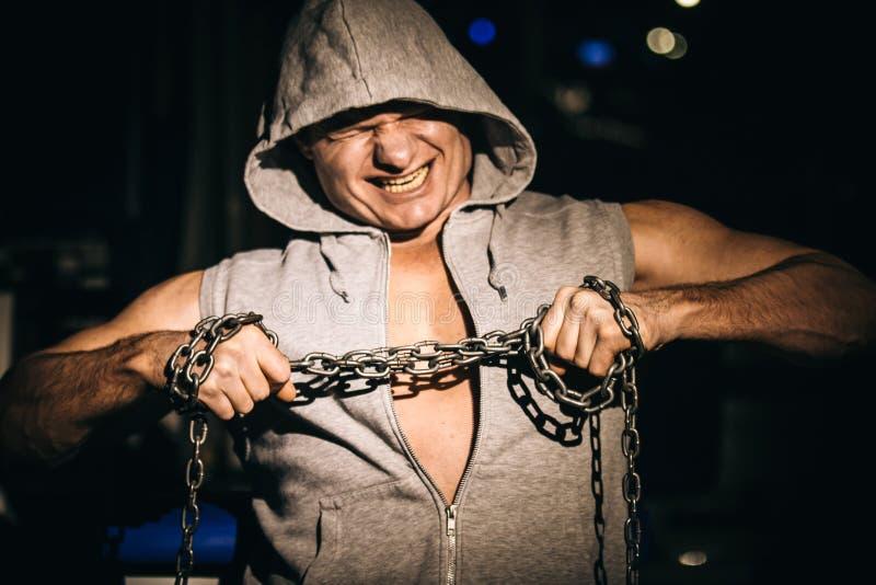 Porträt des aggressiven Bodybuilders versuchend, die Metallkette zu zerreißen stockbild