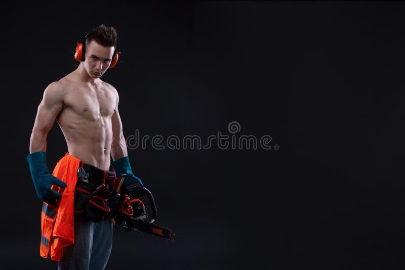 Porträt des aggressiven muskulösen Mannes mit Kettensäge in der Hand, werfend auf schwarzem Hintergrund auf Erbauer lizenzfreies stockbild