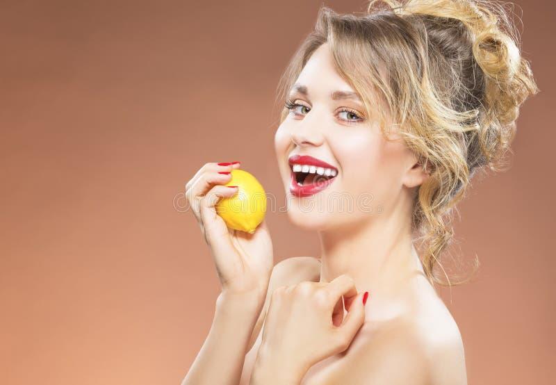 Porträt des Anziehens der sexy kaukasisches blondes Mädchen-beißenden Zitrone stockfoto