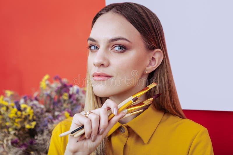 Porträt des Appellierens von blond-haarigen Künstlerholding-Malereibürsten stockfotos
