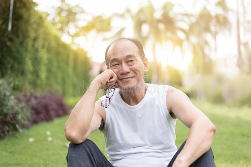 Porträt des asiatischen älteren Mannes, der auf Gras am Th sich entspannt und sitzt stockfotos