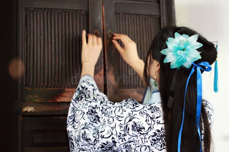 Porträt des asiatischen chinesischen Mädchens im Trachtenkleid, tragen blaue und weiße Porzellanart Hanfu, offener alter Schrank stockbilder