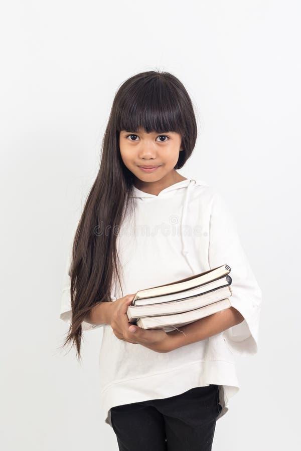 Porträt des asiatischen kleinen Mädchens, das ein Buch auf Weiß hält stockbilder