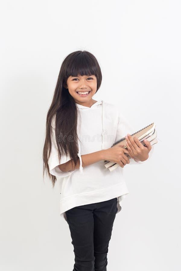 Porträt des asiatischen kleinen Mädchens, das ein Buch auf Weiß hält lizenzfreies stockfoto