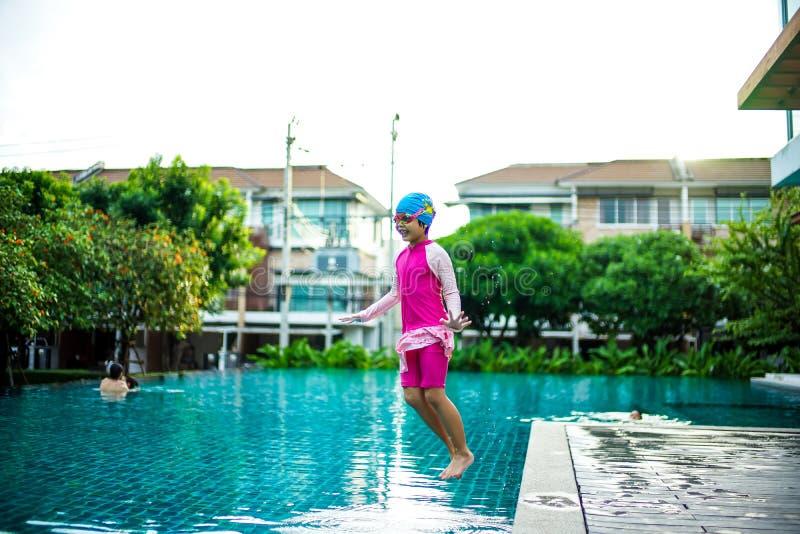 Porträt des asiatischen kleinen Mädchens, das glücklich im Pool schwimmt lizenzfreies stockbild