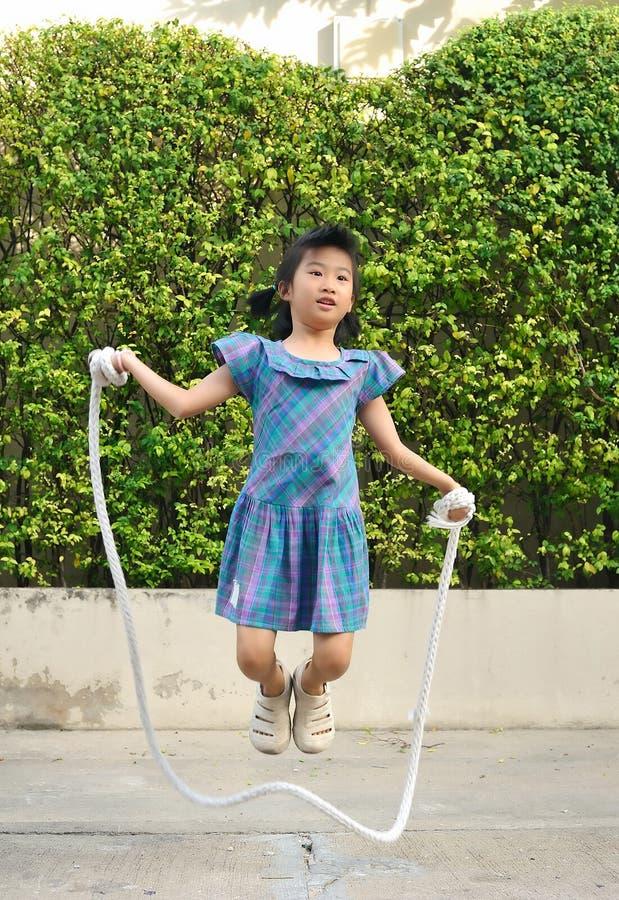Porträt des asiatischen kleinen Mädchens, das handgemachtes Seil unter Schwingen im Park springt lizenzfreie stockfotos
