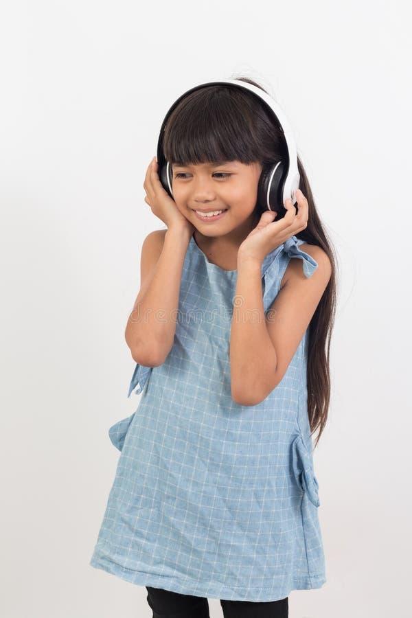Porträt des asiatischen kleinen Mädchens, das Musik hört lizenzfreie stockbilder