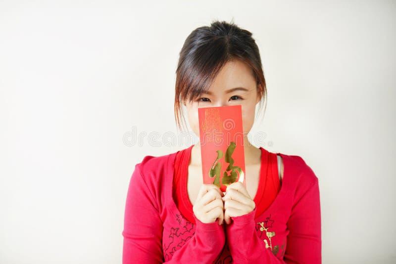 Porträt des asiatischen Mädchens mit roten Umschlägen in ihren Händen stockfoto