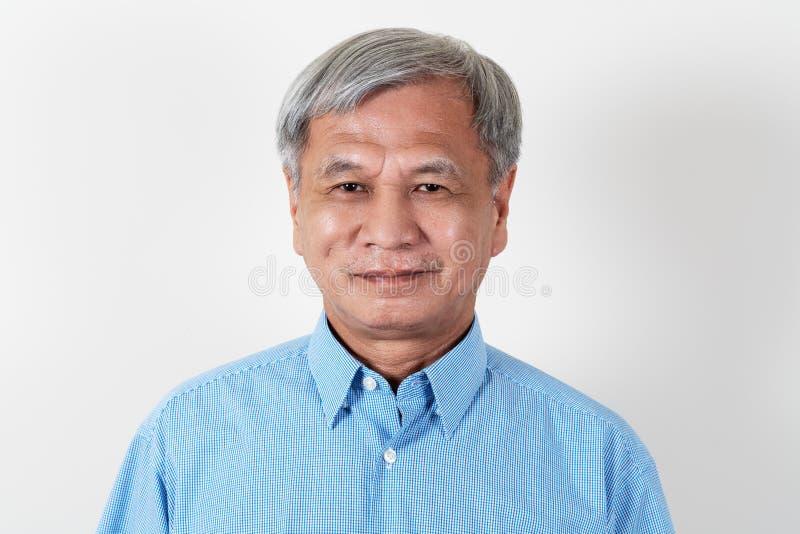Porträt des attraktiven älteren asiatischen Mannes, der Kamera im Studio lächelt und betrachtet lizenzfreies stockfoto
