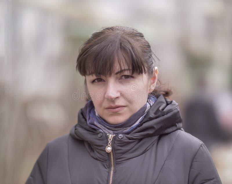 Porträt des attraktiven brunette Mädchens auf dem unscharfen Hintergrund der Straße, die Kamera betrachtend lizenzfreie stockfotografie