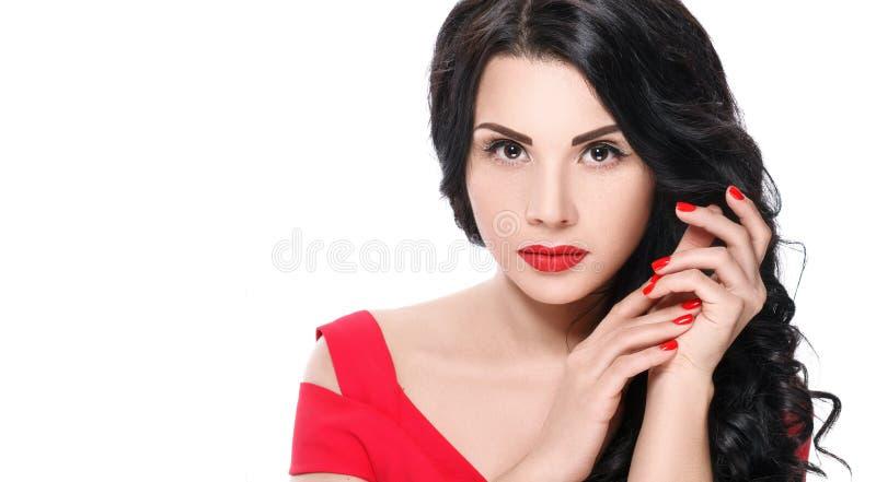 Porträt des attraktiven Brunettemädchens mit den roten Lippen und den roten Nägeln lizenzfreies stockbild