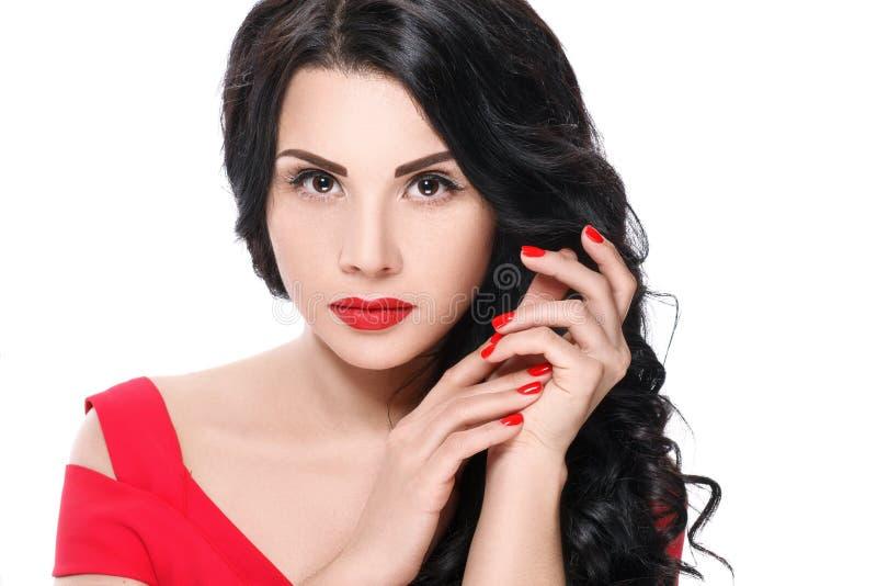 Porträt des attraktiven Brunettemädchens mit den roten Lippen und den roten Nägeln Getrennt auf weißem Hintergrund stockfotografie