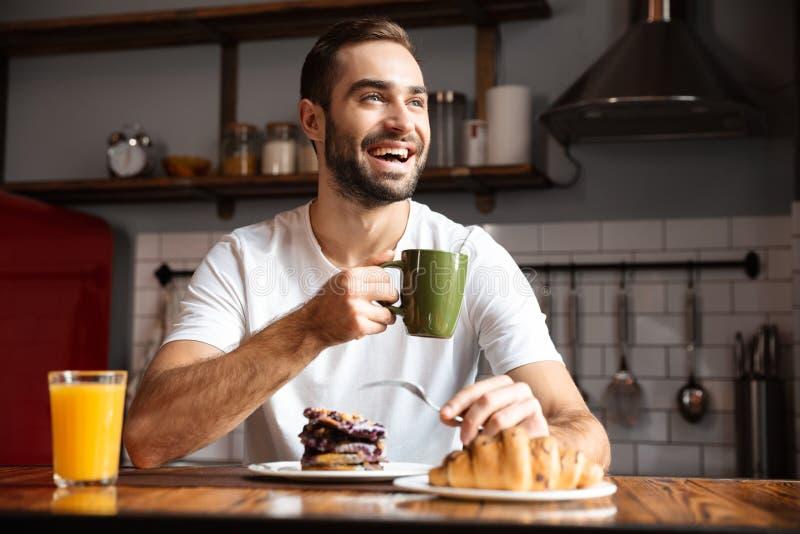 Porträt des attraktiven essenden Mannes 30s beim Frühstücken in der stilvollen Küche zu Hause stockfoto