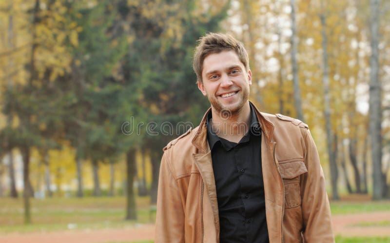 Porträt des attraktiven glücklichen lächelnden stilvollen jungen Mannes im Herbst stockfotografie