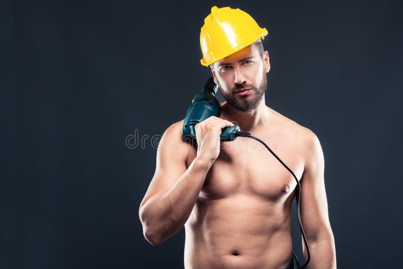 Porträt des attraktiven hemdlosen Arbeiters mit Bohrgerät stockfotos