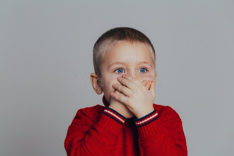 Porträt des attraktiven Jungen in der roten Strickjacke, die seinen Mund mit den Händen bedeckt, schließen oben lizenzfreies stockbild
