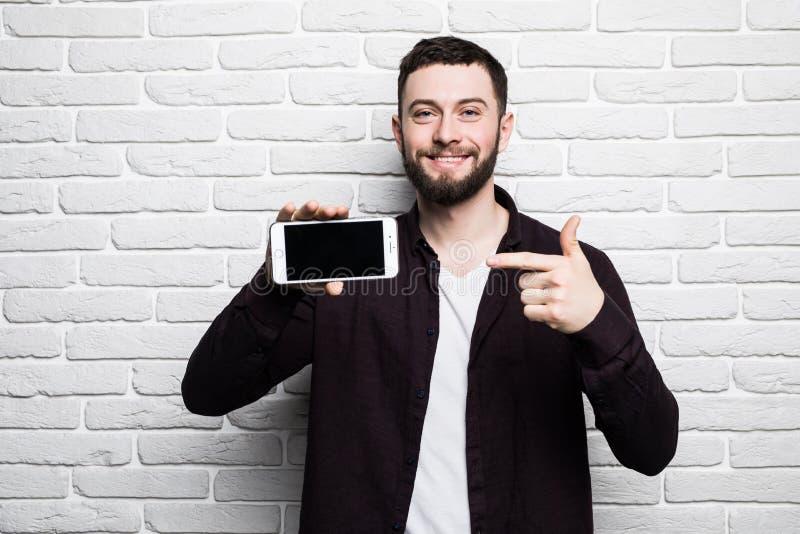 Porträt des attraktiven jungen Geschäftsmannes in der zufälligen Kleidung zeigte ein intelligentes Telefon und in camera schaute  stockbilder