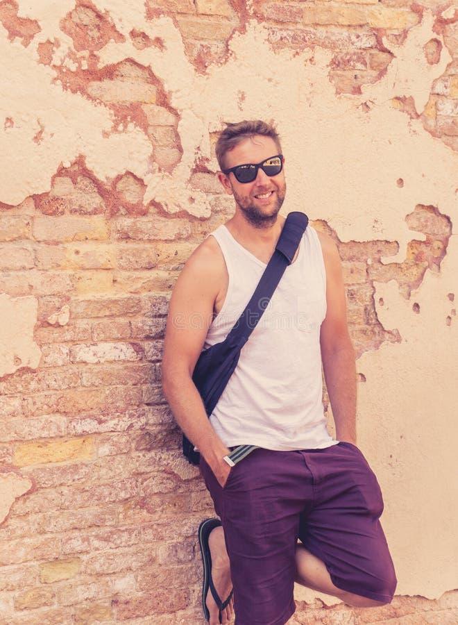 Porträt des attraktiven kühlen jungen Mannes, der auf alter Backsteinmauer sich lehnt lizenzfreie stockbilder