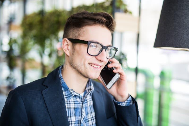 Porträt des attraktiven kaukasischen Mannes im zufälligen Hemd und in den Gläsern sprechend am Mobiltelefon am Arbeitsplatz stockbild