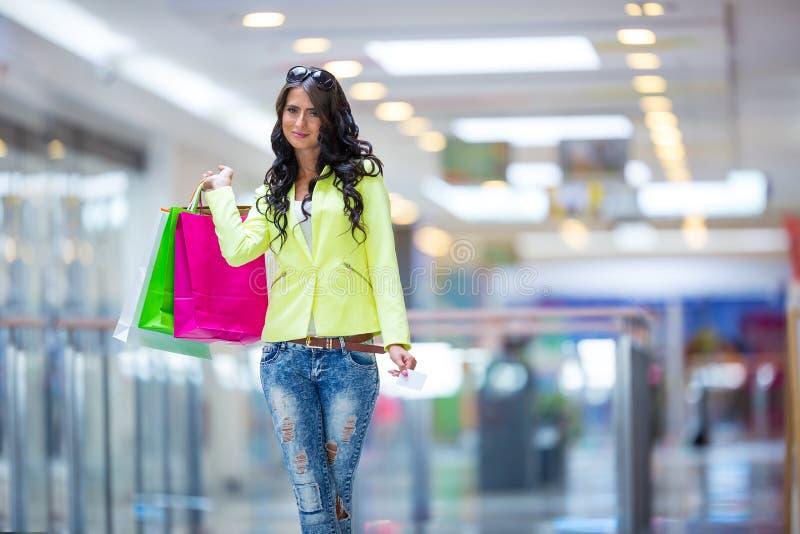 Porträt des attraktiven lächelnden Brunette im Einkaufszentrum mit einer Taschenkreditkarte in einer Hand lizenzfreie stockfotos