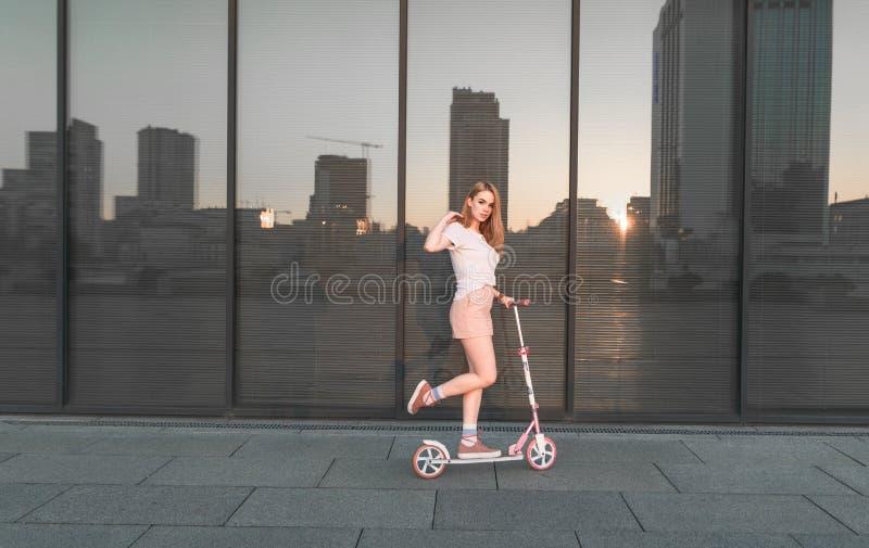Porträt des attraktiven Mädchenreitens auf rosa Roller gegen Hintergrund der dunklen Glaswand, Reflexion der Sonne und Stadt stockfoto