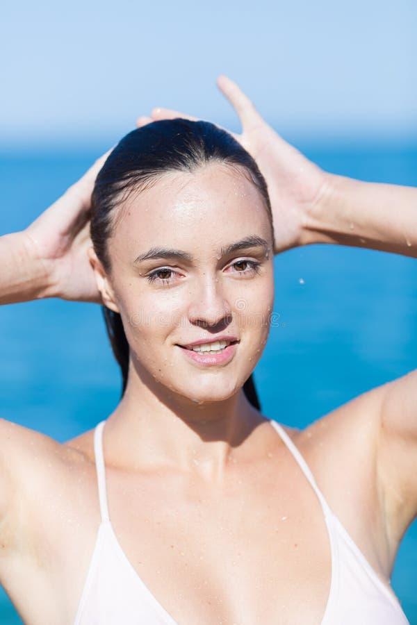 Porträt des attraktiven Mädchens im Badeanzug mit den Händen hinter Kopf lizenzfreie stockbilder