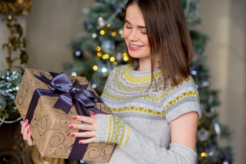 Porträt des attraktiven Mädchens im Pullover, der Geschenkbox hält stockbild