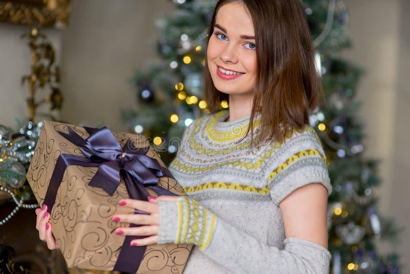 Porträt des attraktiven Mädchens im Pullover, der Geschenkbox hält lizenzfreie stockfotos